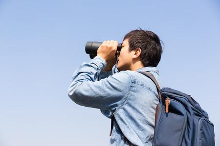 using binoculars: Man using binoculars with clear blue sky