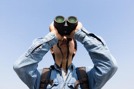 using binoculars: Young Man using binoculars with clear blue sky
