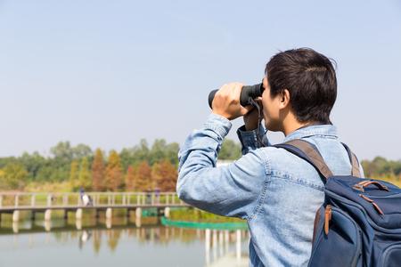 Young Man use of the binocular Banco de Imagens