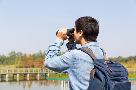 using binoculars: The back rear of man using binoculars for birdwatching Stock Photo