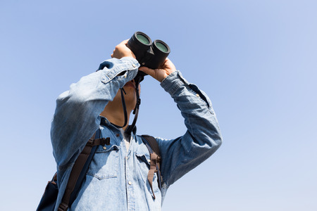 though: Young Man looking though binoculars with clear blue sky