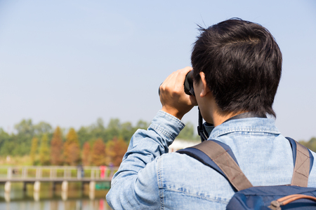 using binoculars: The back rear of man using binoculars Stock Photo