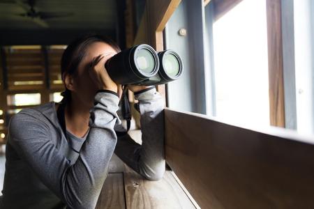 birdwatching: Asian woman using binoculars for birdwatching Stock Photo