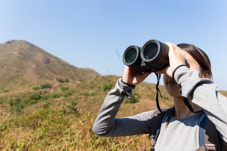 though: Woman looking though binocular when going hiking