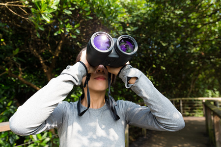 though: Woman looking though binoculars at jungle