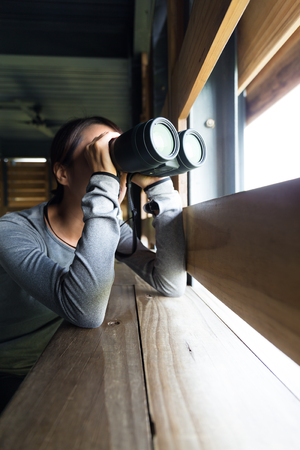 using binoculars: Woman using binoculars for birdwatching at wooden house Stock Photo