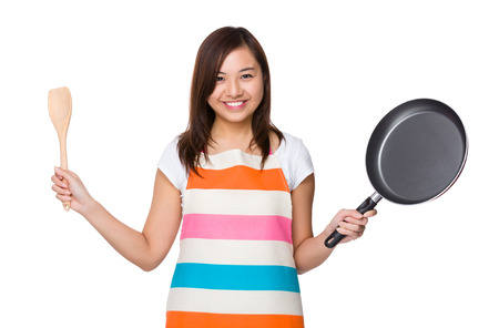 pan asian: Asian Housewife holding up with wooden ladle and frying pan Stock Photo