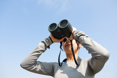 though: Woman looking though telescope Stock Photo