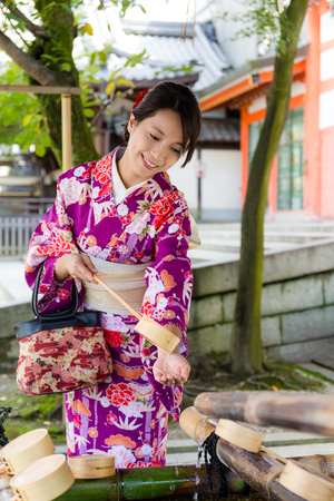 go inside: Japanese woman washing hand before go inside the temple