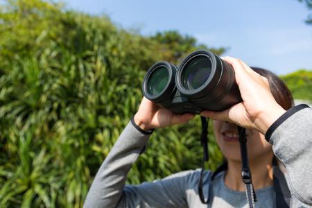 bird watching: Young Woman use of the binoculars for bird watching