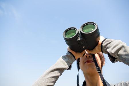 though: Woman watching though binoculars