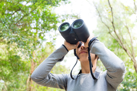 Woman looking though the binocular