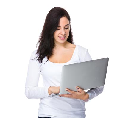 sweatsuit: Brunette woman read on the laptop computer Stock Photo