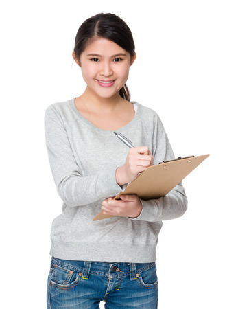 sweatsuit: Young Woman write on clipboard Stock Photo