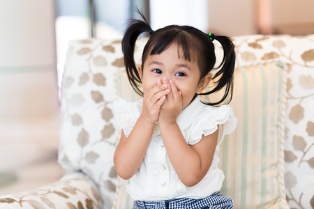 hand in mouth: Happy girl with hand cover her mouth Stock Photo