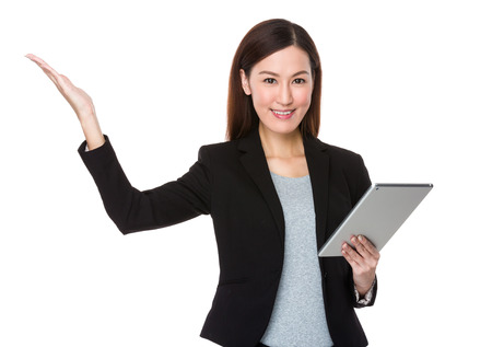 promoting: Young businesswoman use of tablet pc and open hand palm for promoting something
