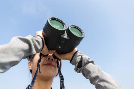though: Woman watching though binoculars with clear blue sky