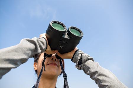 though: Woman watching though telescope Stock Photo