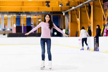 Young woman make balance on skating rink