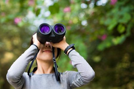 though: Woman looking though binocular in jungle