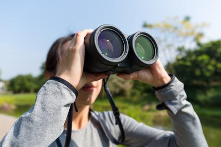 though: Asian Woman looking though binoculars
