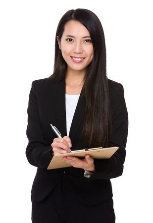 Asiática joven empresaria tome nota en el portapapeles