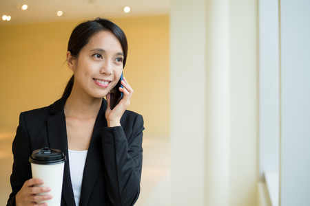 hot secretary: Asian Businesswoman talk to mobile phone and holding coffee Stock Photo
