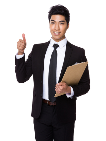 joyful businessman: Asian businessman holding with file board and thumb up