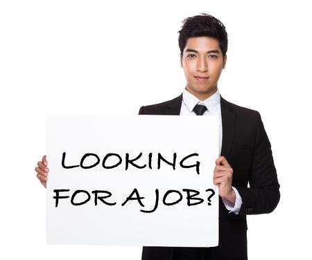 Hombre de negocios asiático que muestra un cartel que muestra con la búsqueda de un empleo frases