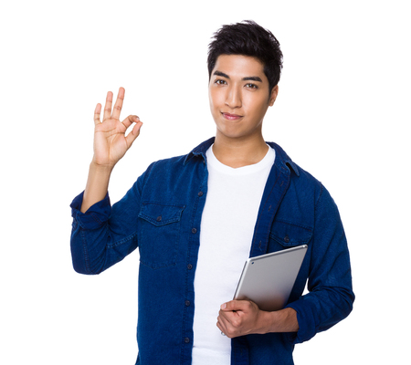 アジア混合インド人保持ラップトップ コンピューターと ok の手話 写真素材