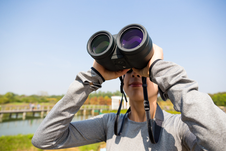 though: Woman looking though binocular for bird watching Stock Photo