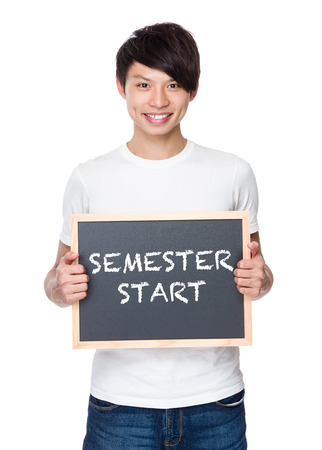 semester: Young man hold with chalkboard showing phrase of semester start