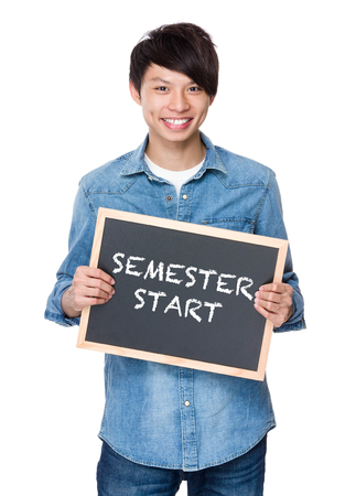 semester: Asian young man with chalkboard showing phrase of semester start