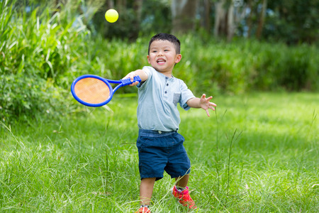 excite: Excite Little boy play with tennis at park Stock Photo