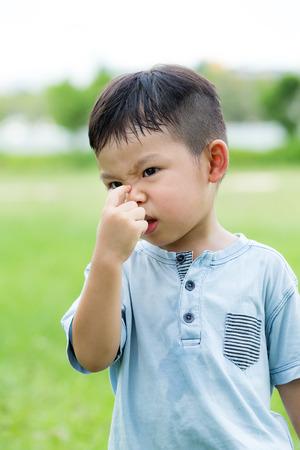olfato: Niño pequeño que sostiene la nariz de mal olor Foto de archivo