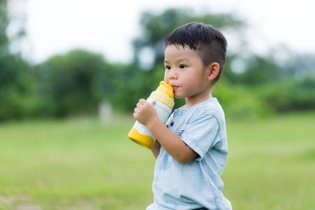 Little boy drink of water with plastic bottle