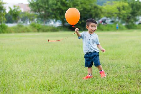 little people: Little boy holding balloon