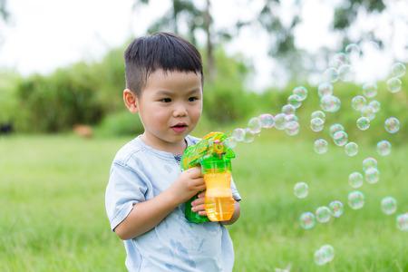 niños chinos: Juego del niño asiático con el ventilador de la burbuja