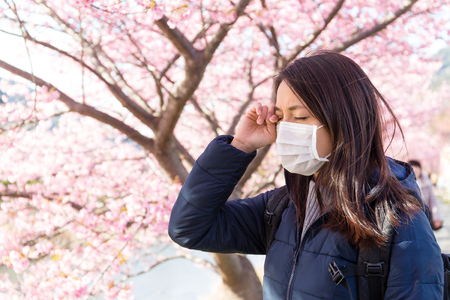Woman suffer from Pollen allergy under sakura tree