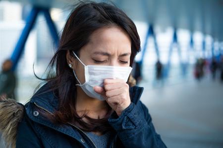 Vrouw last heeft van hoesten met bescherming masker Stockfoto