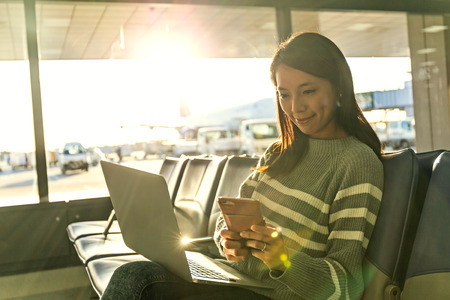 Woman look at cellphone with her laptop at airport
