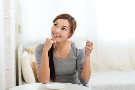 far away look: Young Woman holding a cup of tea and look far away Stock Photo