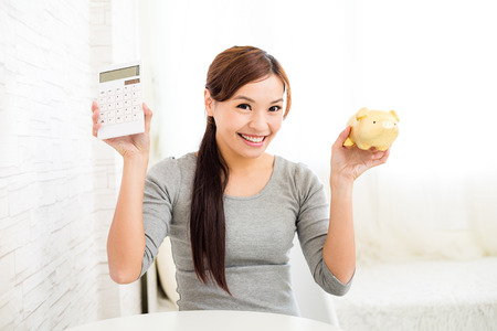 calculator chinese: Woman showing calculator and piggy bank Stock Photo