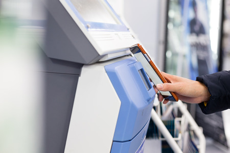 ticketing: Woman connecting mobile phone and ticketing machine by NFC Stock Photo