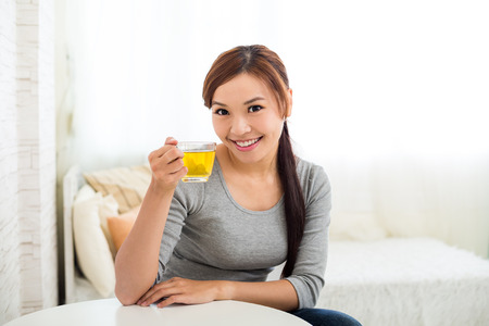 sit up: Woman drinking a cup of tea Stock Photo