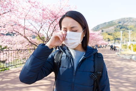 Woman suffer from allergy from pollen allergy at sakura season