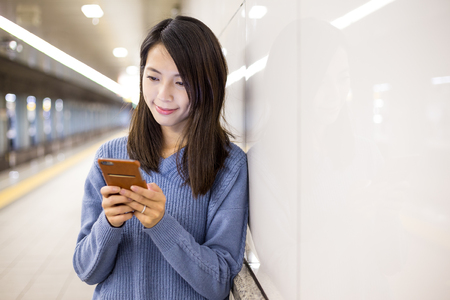 Woman use of mobile phone in underground subway station 免版税图像