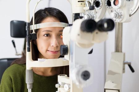 Mujer que controla la visión con el equipo Foto de archivo - 53804224