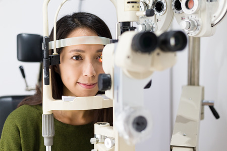 Woman checking vision with equipment