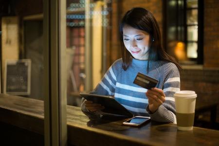 factura: Mujer joven que usa la tarjeta de crédito para el pago en la tablilla